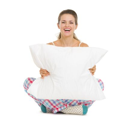 Happy young woman in pajamas sitting with pillow Stock Photo - 17137333