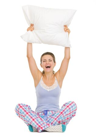 Cheerful young woman in pajamas sitting and holding pillow Stock Photo - 17137458