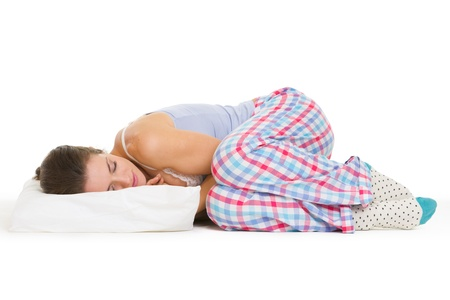 Young woman in pajamas sleeping on pillow isolated on white Stock Photo - 17137438