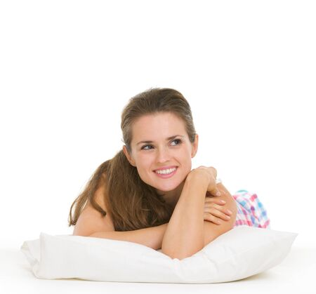 Happy young woman in pajamas laying on pillow and looking on copy space Stock Photo - 17137412