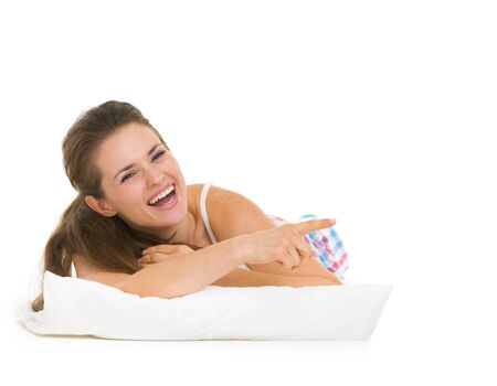 Happy young woman in pajamas laying on pillow and pointing on copy space Stock Photo - 17137413