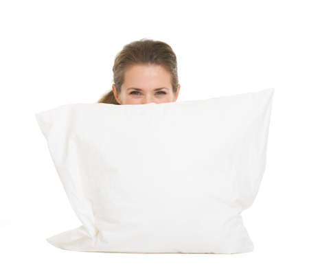 Woman hiding behind pillow isolated on white Stock Photo - 17137336