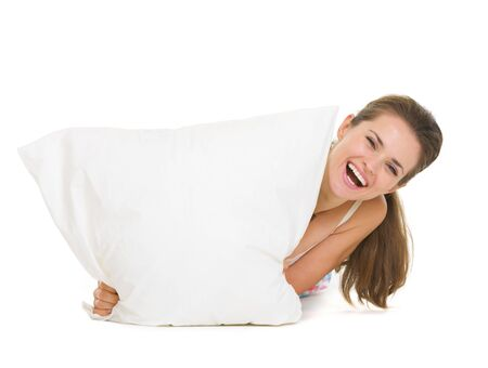 Woman looking out from pillow isolated on white Stock Photo - 17137375
