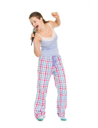 Full length portrait of young woman in pajamas singing in microphone photo