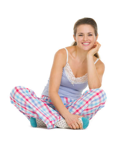 Young woman in pajamas sitting on floor isolated on white Stock Photo - 17137439