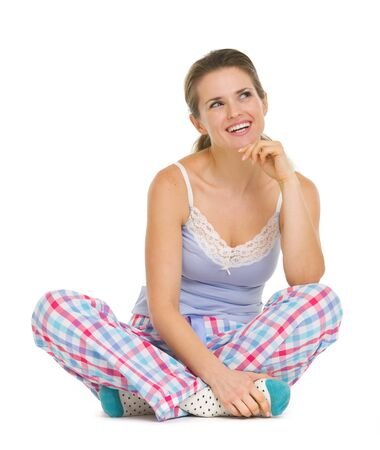 stargaze: Thoughtful young woman in pajamas sitting on floor and looking on copy space