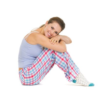 Happy young woman in pajamas sitting on floor isolated on white Stock Photo - 17137442