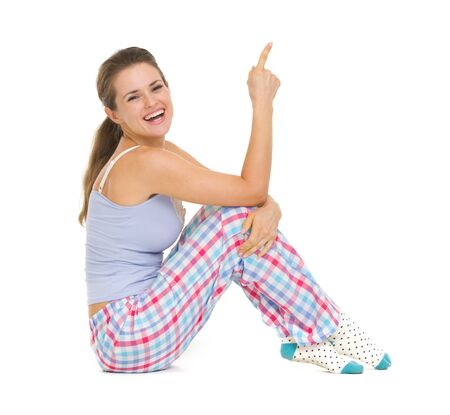 Smiling young woman in pajamas sitting on floor and pointing on copy space Stock Photo - 17137446