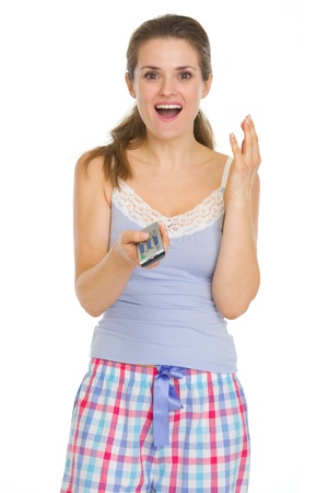 Surprised young woman in pajamas with TV remote control Stock Photo - 17137462