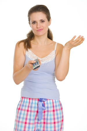 Bored young woman in pajamas holding TV remote control Stock Photo - 17137399