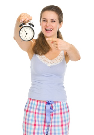 Happy young woman in pajamas pointing on alarm clock Stock Photo - 17137417