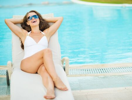 Happy young woman in swimsuit laying on chaise-longue poolside Stock Photo - 17283136