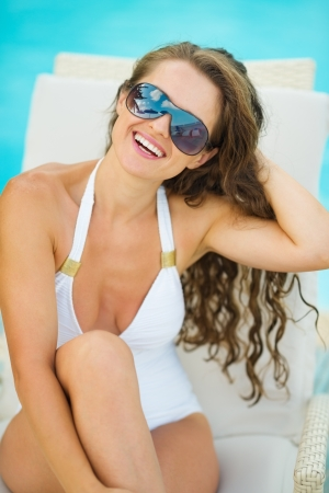 Portrait of smiling young woman in swimsuit relaxing on chaise-longue Stock Photo - 17283154