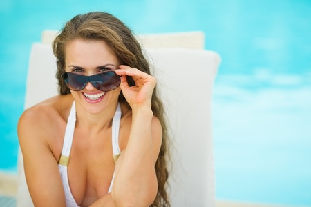 Portrait of happy young woman in swimsuit relaxing on chaise-longue Stock Photo - 17283129