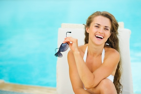 Portrait of happy young woman in swimsuit relaxing poolside Stock Photo - 17283126