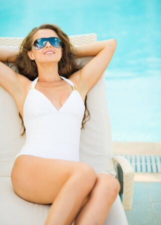Young woman in swimsuit laying on chaise-longue poolside Stock Photo - 17283117