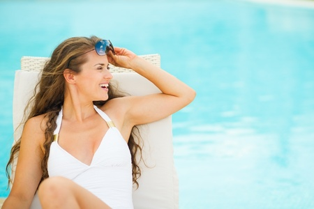 Happy young woman in swimsuit on chaise-longue and looking on copy space Stock Photo - 17283125