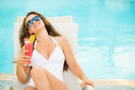 Young woman in swimsuit relaxing with cocktail on chaise-longue Stock Photo - 17283134