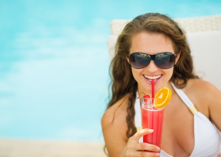 Portrait of happy young woman in swimsuit drinking cocktail Stock Photo - 17283114