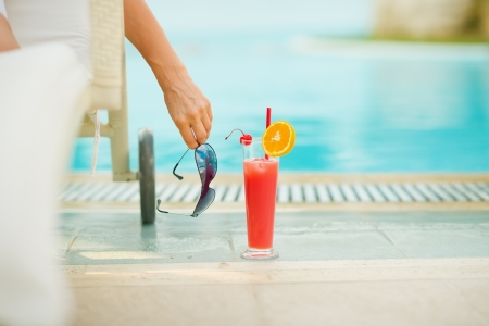 Closeup on cocktail near chaise-longue with relaxing woman Stock Photo - 17283139