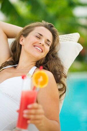 Happy young woman in swimsuit relaxing with cocktail on chaise-longue Stock Photo - 17283161