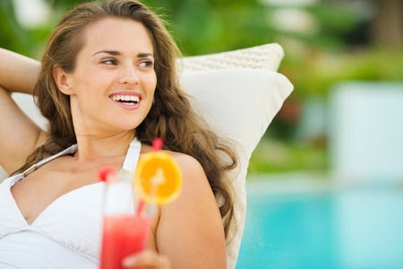 Smiling young woman in swimsuit with cocktail looking on copy space Stock Photo - 17283163