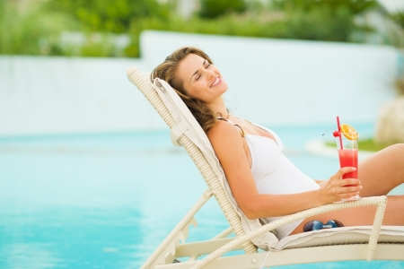 swimming suit: Young woman in swimsuit relaxing with cocktail on chaise-longue