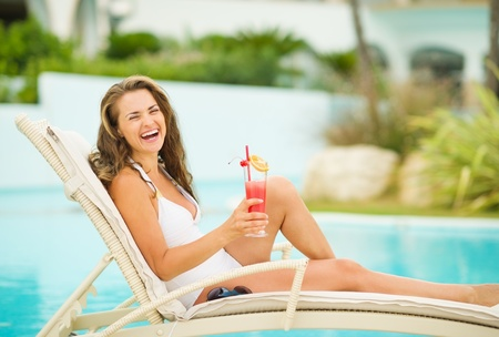 Smiling young woman in swimsuit relaxing with cocktail on chaise-longue