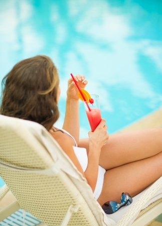 Woman relaxing on chaise-longue with cocktail. Rear view Stock Photo - 17283135