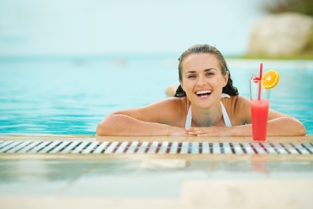 Smiling young woman relaxing in pool with cocktail Stock Photo - 17283131