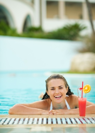 Happy young woman relaxing in pool with cocktail Stock Photo - 17283132