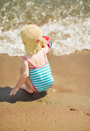 Baby playing near sea. Rear view Stock Photo - 17283168