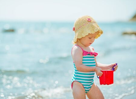 Baby playing with pail near sea photo