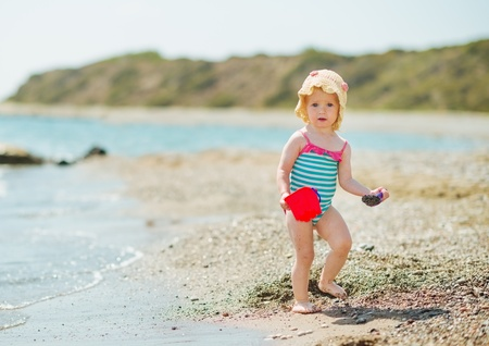 Baby playing with pail on sea shore Stock Photo - 17283140