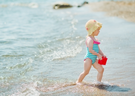 Baby playing with pail on seashore photo