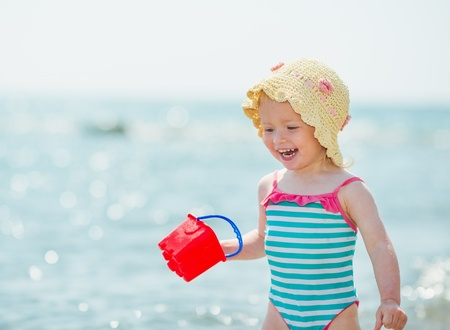 Smiling baby playing with pail on seashore photo