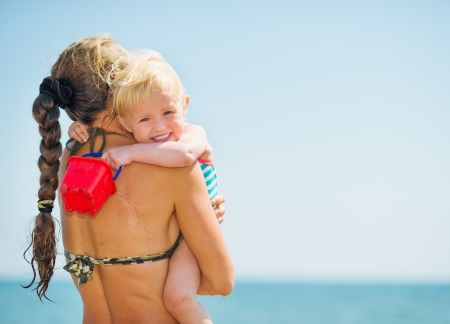 Baby hugging mother on sea beach Stock Photo - 17283144