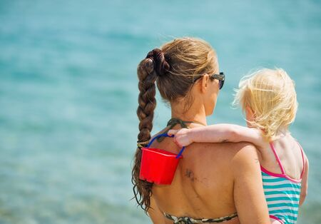 Mother and baby looking on sea. Rear view Stock Photo - 17283164