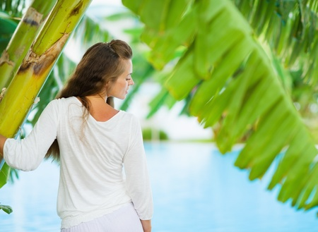 Young woman relaxing among tropical palms. Rear view Stock Photo - 17283121