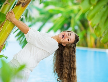 Laughing young woman leaning on tropical palm Stock Photo - 17283146