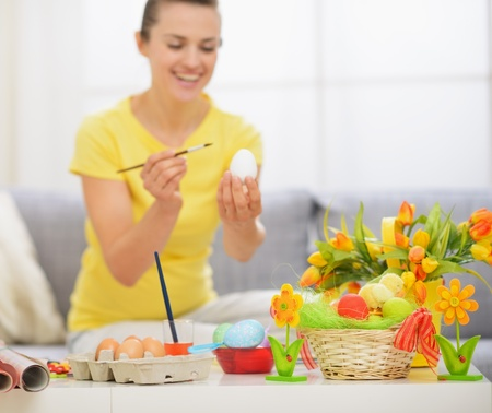 Closeup on table with Easter decoration and woman drawing on egg in background Stock Photo - 17304848