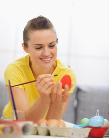 Happy young woman drawing on Easter red egg Stock Photo - 17304867
