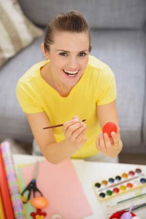 Smiling young woman drawing on Easter red egg Stock Photo - 17304825