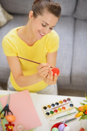 Happy young woman drawing on Easter red egg photo
