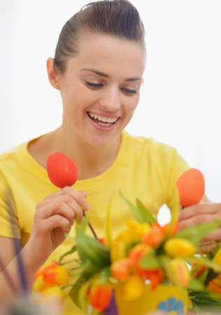 Happy young woman making Easter decoration with tulips and eggs Stock Photo - 17304852