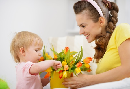 Happy mother and baby making decoration with bouquet of tulips in bucket Stock Photo - 17304830