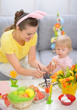 Happy mother and baby painting on Easter eggs Stock Photo - 17304853