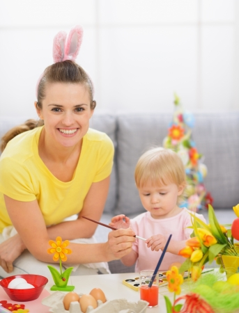 Happy mother and baby painting on Easter eggs photo