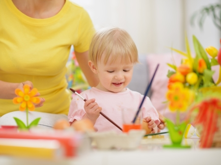 Happy mother and baby making Easter decorations Stock Photo - 17304856