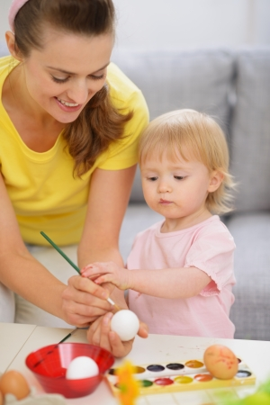 Happy mother and baby painting on Easter eggs Stock Photo - 17304845